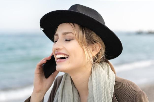 彼女の携帯電話で話し、スタイリッシュな帽子で笑っている陽気な笑顔の若い女性の肖像画