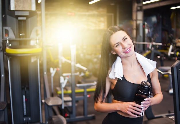 Портрет веселой улыбающейся молодой спортсменки в спортивной одежде и полотенце на шее, с бутылкой воды в руке в тренажерном зале. позитивные эмоции