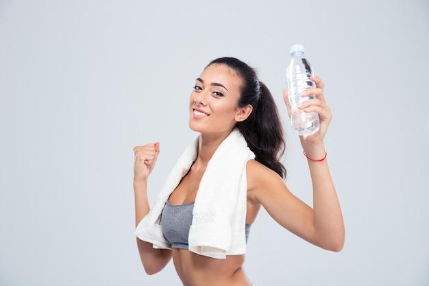 Портрет веселой спортивной женщины с полотенцем, держащей бутылку с водой, изолированной на белой стене