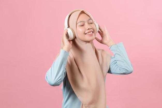 ピンクの背景の上に孤立して立っている、ヘッドフォンで音楽を聴いて、踊ってヒジャーブを身に着けている陽気なスタイリッシュな若いイスラム教徒の女性の肖像画