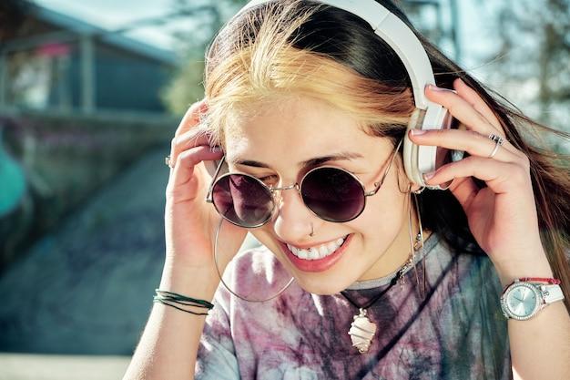 ヘッドフォンで音楽を聴いて笑顔で陽気なスタイリッシュな若い女性の肖像画