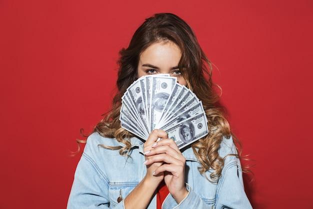 赤い壁の上に孤立して立っている、ポーズをとって、お金の紙幣を見せて、カバーの顔にデニムジャケットを着て陽気なスタイリッシュな若い女性の肖像画