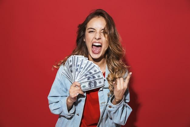赤い壁の上に孤立して立っている、ポーズをとって、お金の紙幣を見せて、彼女の舌を突き出してデニムジャケットを着ている陽気なスタイリッシュな若い女性の肖像画