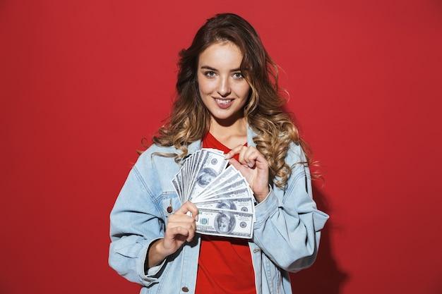 赤い壁の上に孤立して立って、ポーズをとって、お金の紙幣を見せてデニムジャケットを着て陽気なスタイリッシュな若い女性の肖像画