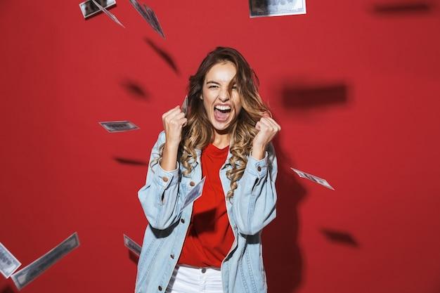Портрет веселой стильной молодой женщины в джинсовой куртке, стоящей изолированно над красной стеной, стоящей под дождем банкнот денег