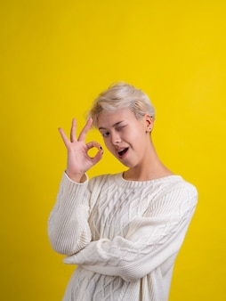 白いニットのセーターを着た陽気な10代の少女の肖像画は、大丈夫なジェスチャーとウインクをします