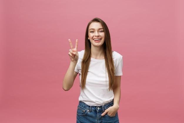 Портрет веселой модной женщины, показывающей два пальца, подписывает o