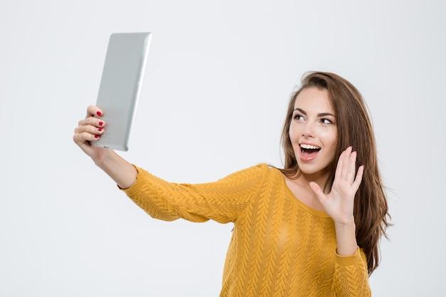 白い背景で隔離のタブレット コンピューターでビデオ通話をしている陽気な女性の肖像画