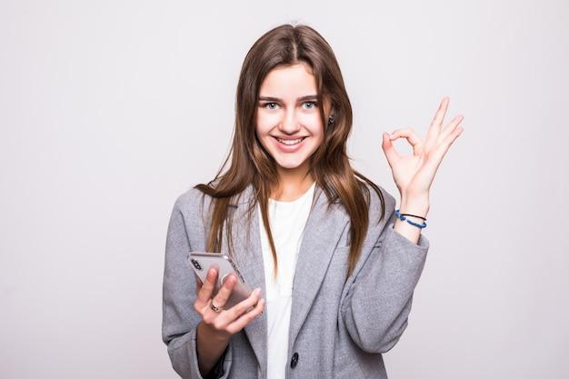 立っていると白い背景に分離されたokのしぐさを見せながら空白の画面の携帯電話を保持している陽気な女性の肖像画