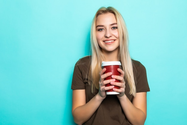 緑の壁にコーヒーとカップを保持している陽気な女性の肖像画。