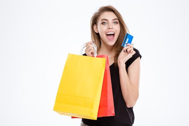 Портрет веселой женщины, держащей хозяйственные сумки и кредитную карту, изолированные на белом фоне