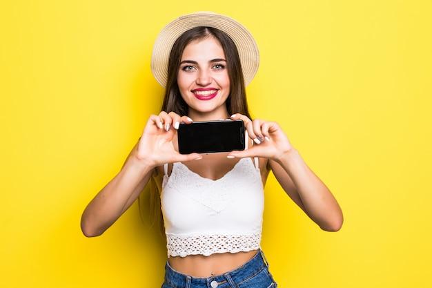 黄色の壁に空白のスマートフォンの画面を示す陽気な女性の肖像画。