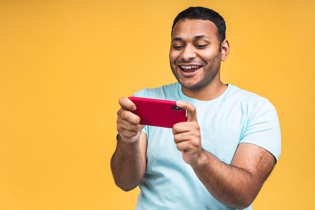 黄色の背景で隔離の携帯電話でカジュアルなプレイゲームに身を包んだ陽気な若いアフリカの黒人インド人の肖像画。