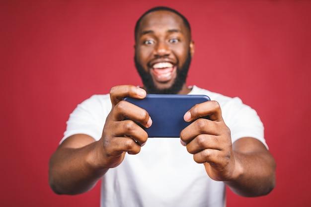 Портрет жизнерадостного молодого африканского человека одел в вскользь играя играх на мобильном телефоне изолированном над красной предпосылкой.