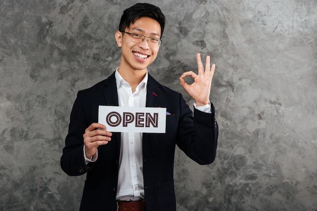 Портрет жизнерадостного молодого азиатского человека одетого в костюм