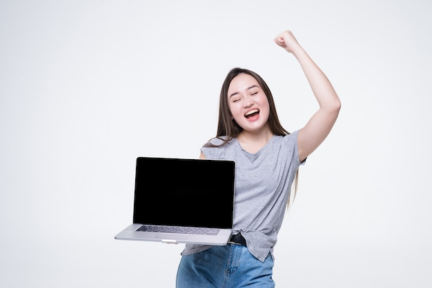흰 벽 위에 절연 빈 화면 노트북에서 쾌활한 젊은 아시아 여자 가리키는 손가락의 초상화