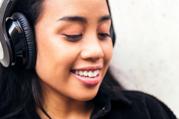 야외에서 음악을 들으며 헤드폰을 끼고 있는 쾌활한 젊은 아시아 여성의 초상화