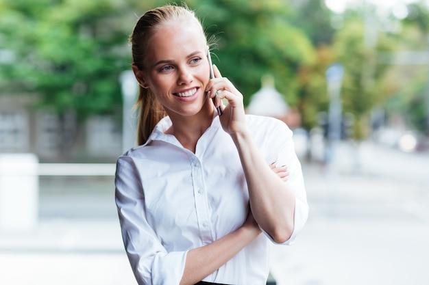 Портрет веселой молодой деловой женщины с мобильным телефоном разговаривает на открытом воздухе