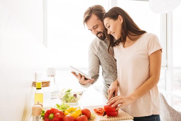 サラダを調理する陽気な若いカップルの肖像画