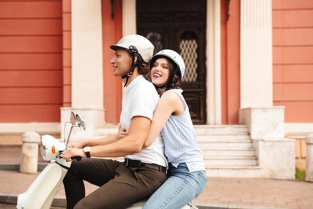 街の通りで一緒にバイクに乗ってヘルメットをかぶった陽気な若いカップルの肖像画