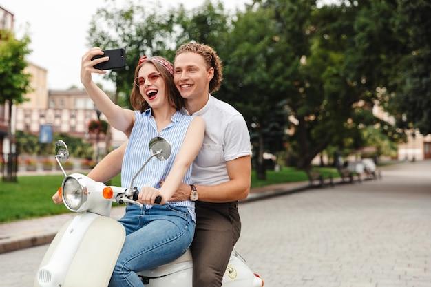 Портрет веселой молодой пары, вместе катающейся на мотоцикле по городской улице, делающей селфи