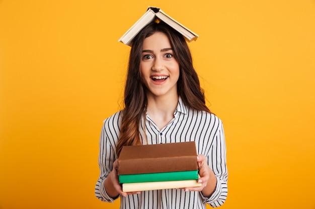 Портрет веселая молодая девушка держит книги