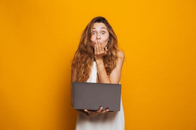 Портрет веселой молодой девушки, держащей портативный компьютер