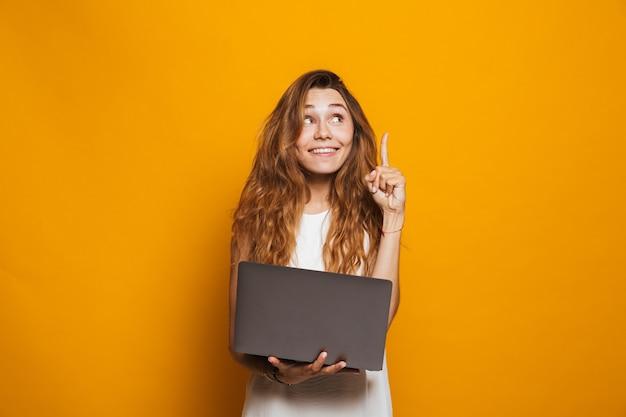 Портрет веселой молодой девушки, держащей ноутбук