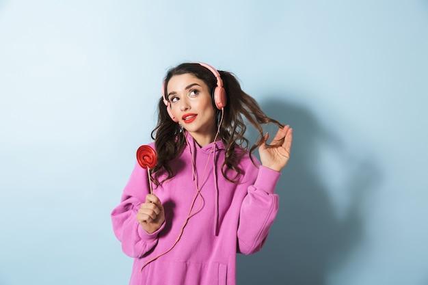 Портрет веселой молодой девушки в толстовке с капюшоном, стоящей над синим, в наушниках и с леденцом в руках