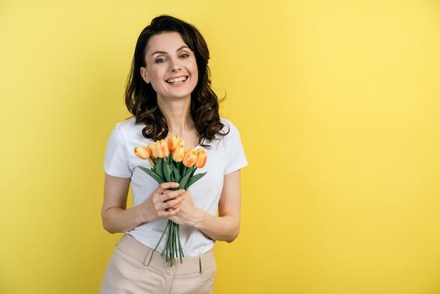 黄色いチューリップの花束と陽気な少女の肖像画