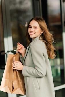 Портрет веселой молодой леди, держащей на открытом воздухе сумки для покупок