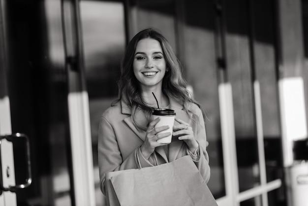 야외 쇼핑 가방을 들고 쾌활 한 젊은 아가씨의 초상