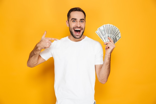 Портрет веселого молодого человека, стоящего изолированно над желтой стеной, показывая денежные банкноты, указывая