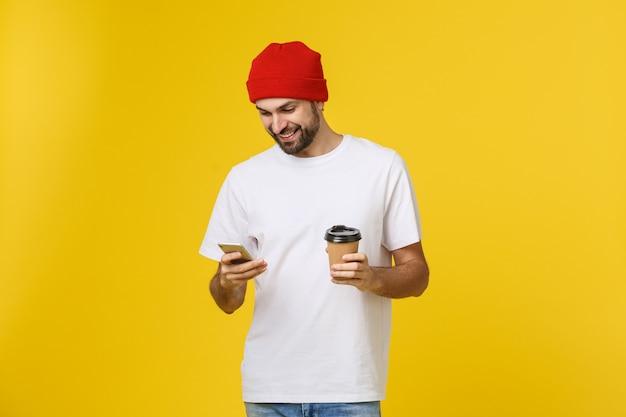 Портрет веселого молодого человека в повседневной одежде, стоящего изолированно над желтым пространством, держащего мобильный телефон и пьющего кофе на вынос