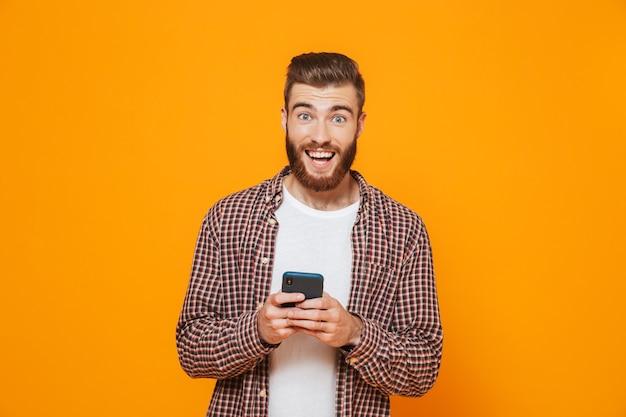 携帯電話を使用してカジュアルな服を着ている陽気な青年の肖像画