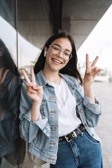 Портрет жизнерадостной молодой красивой студентки в очках гуляет на свежем воздухе, отдыхая, слушая музыку с наушниками, показывая жест мира