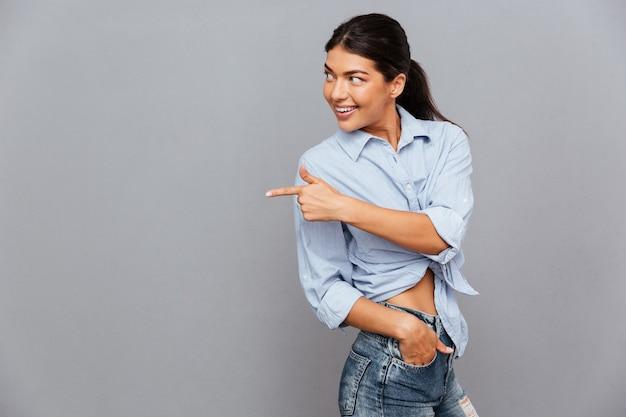Портрет веселой молодой улыбающейся женщины, указывающей пальцем вдали, изолированной на серой стене