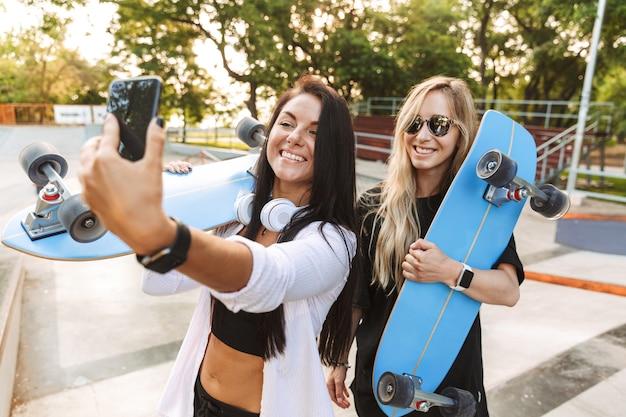 携帯電話を使用してスケートボードで屋外の公園で陽気な若い10代の女の子のスケーターの友人の肖像画は自分撮りを取ります。