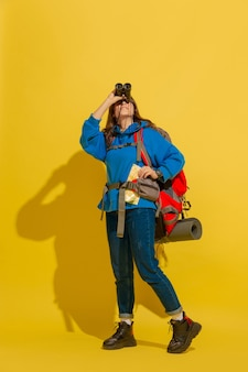 Портрет веселой молодой туристической девушки с сумкой и биноклем, изолированной на желтой стене студии