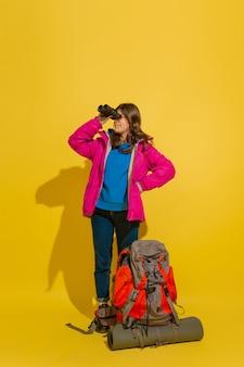 黄色のスタジオの壁に分離されたバッグと双眼鏡で陽気な若い観光の女の子の肖像画