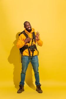 黄色のスタジオの壁に分離されたバッグと双眼鏡を持つ陽気な若い観光客の男の肖像画
