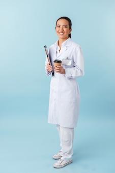 クリップボードを保持し、コーヒーを飲む青い壁の上に孤立してポーズをとって陽気な若い女性医師の肖像画。