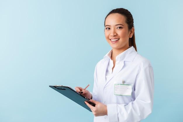 クリップボードを保持している青い壁の上に孤立してポーズをとって陽気な若い女性医師の肖像画。