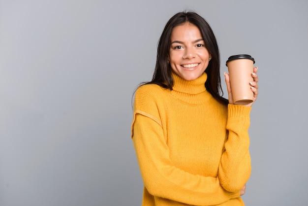회색 벽 위에 절연 테이크 아웃 커피 컵을 들고 스웨터를 입은 쾌활한 젊은 여자의 초상화