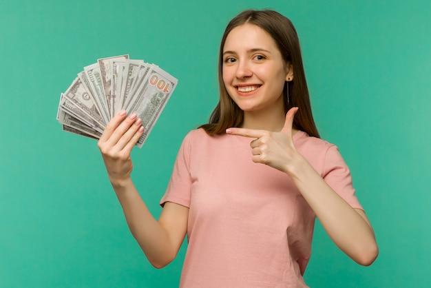 お金の紙幣を保持し、青い背景で隔離を祝う陽気な若い女性の肖像画