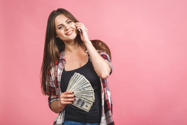 돈 지폐를 들고와 분홍색 배경 위에 절연 축하 쾌활한 젊은 여자의 초상화. 휴대 전화를 사용합니다.