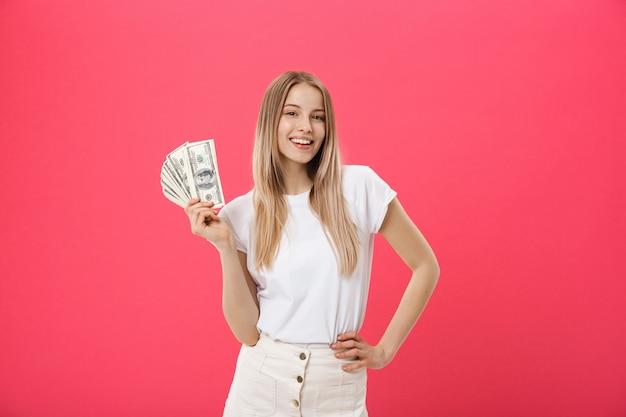Портрет веселая молодая женщина держит деньги банкноты и празднование, изолированных на розовом фоне