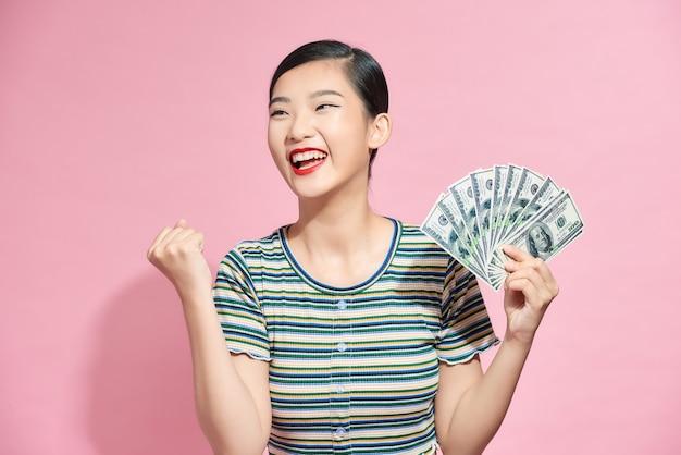 お金の紙幣を保持し、ピンクの上に孤立して祝う陽気な若い女性の肖像画