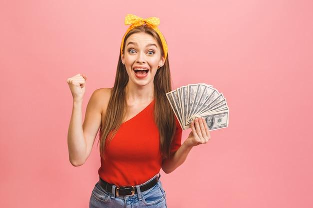 お金の紙幣を持って祝う陽気な若い女性の肖像画
