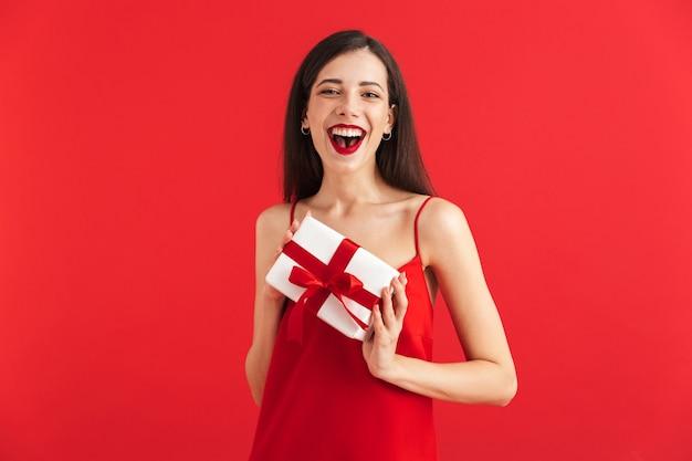 고립 된 선물 상자를 들고 드레스에 쾌활 한 젊은 여자의 초상화